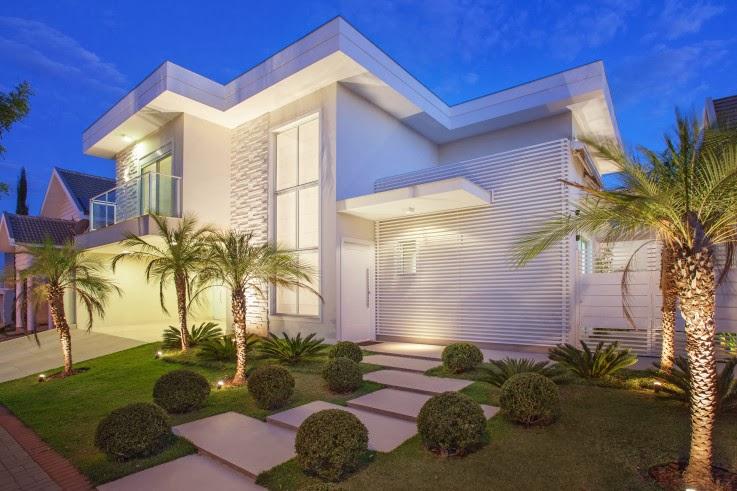 Palmeiras fênix usadas no paisagismo de fachada de casa moderna