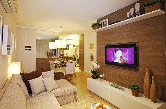 O uso de um material diferenciado como a madeira que cria um destaque para uma das paredes é um artifício comum na decoração de salas pequenas