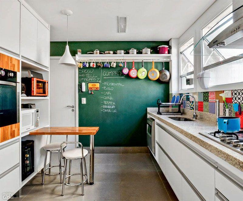 Essa cozinha usa uma parede-quadro para anotar recados aliada a um perfil para pendurar frigideiras e acessórios