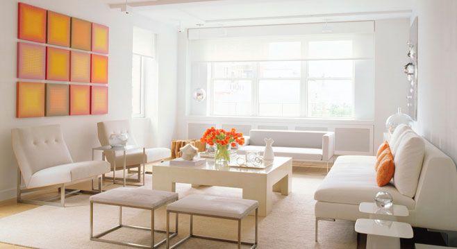 Decoração de sala de estar branca, e para quebrar a monotonia, um painel laranja