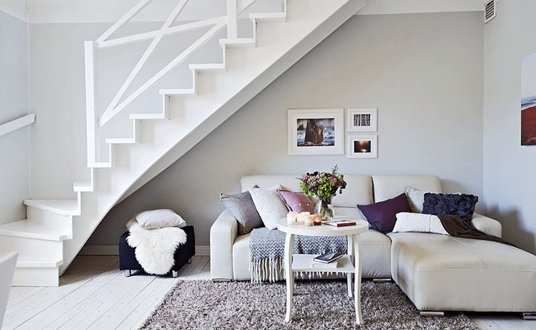 Vão sob a escadaria é completado por sofá aconchegante
