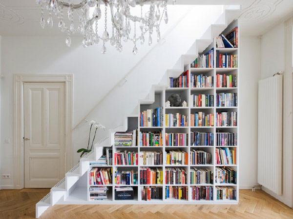 Espaço da escada sendo usado como prateleira de livros