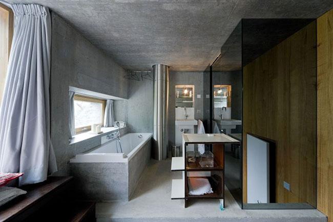 Banheiro mobiliado com paredes e banheira moldadas em concreto