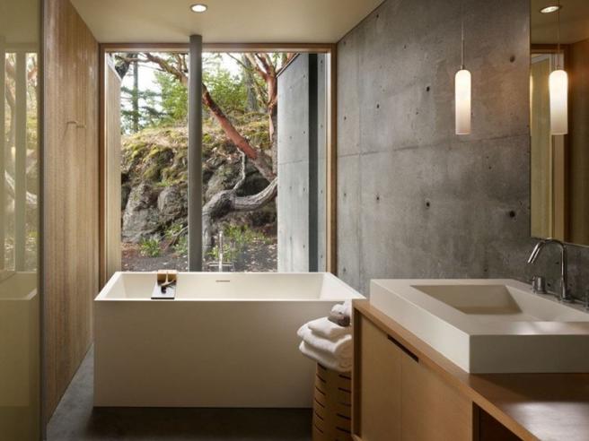 Parede hidráulica de banheiro feita de concreto aparente