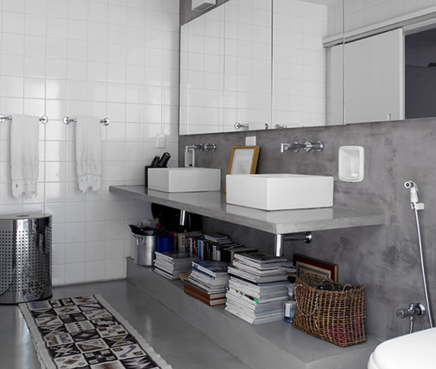 Banheiro com bancada flutuante apoiada em parede de concreto