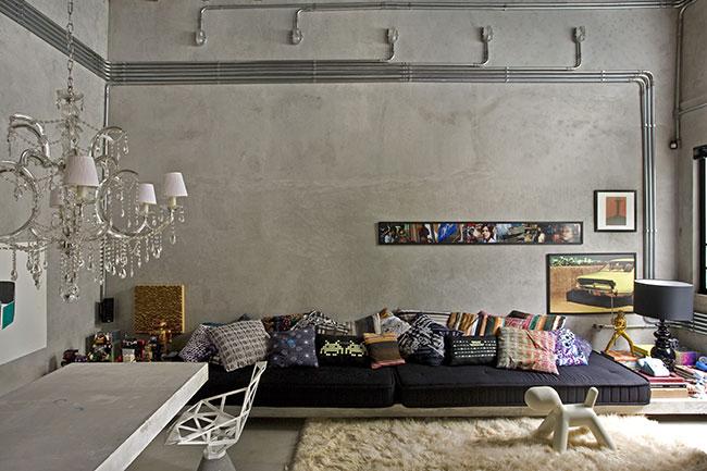 Um belo sofá com iluminação em spots valorizando o ambiente de concreto