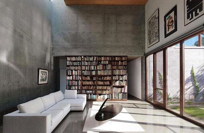 Mini biblioteca interna em sala de estar abrigada por ambiente de concreto aparente