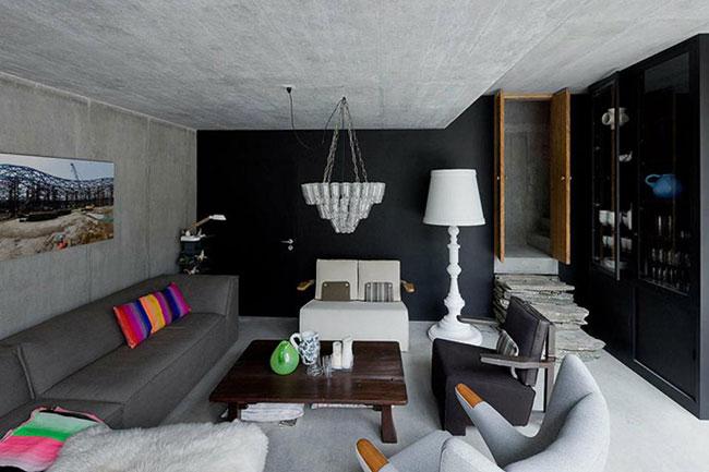 Belo ambiente de estar com parede de fundo preta, e paredes laterais e forro em concreto