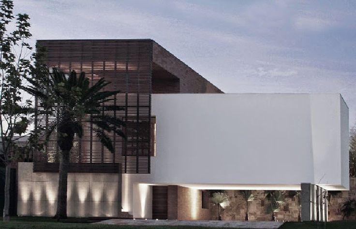 Iluminação ascendente de elemento de pedra externo em fachada de casa contemporânea