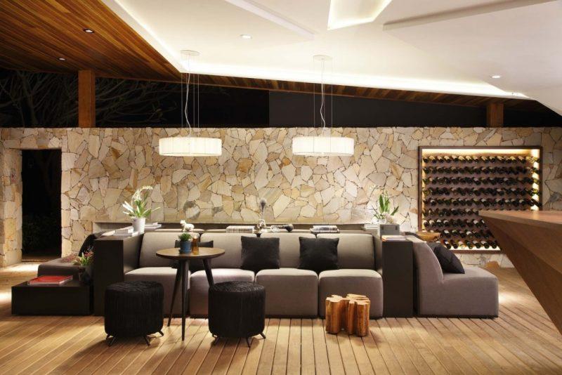 Revestimento da parede de sala de estar fica por conta da pedra São Tomé filetada - ou revestimento canjiquinha - dando um efeito muito mais natural à parede.