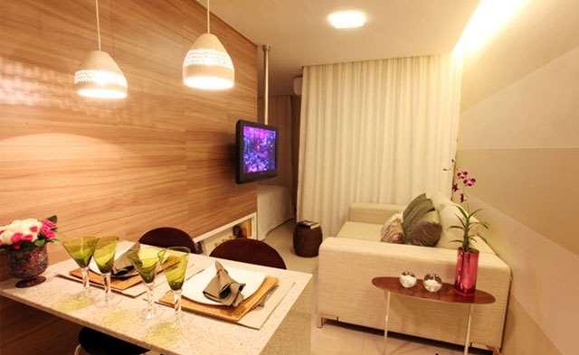 Sala decorada com parede de madeira e forro rebaixado de gesso