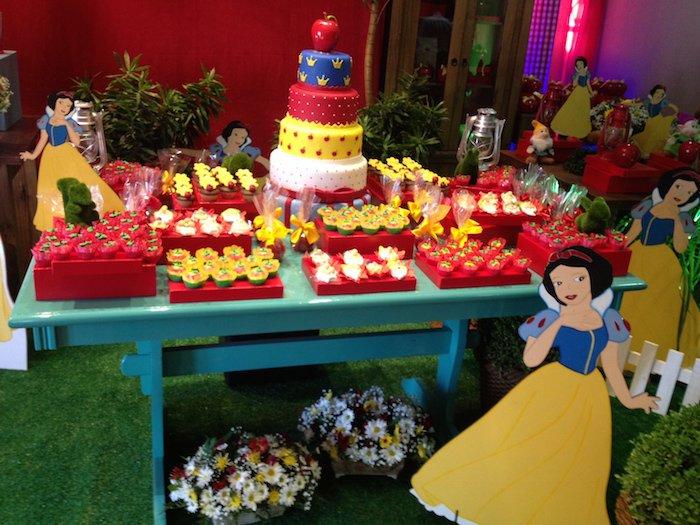 Linda mesa arranjada e bem decorada com docinhos e bolo da Branca de Neve