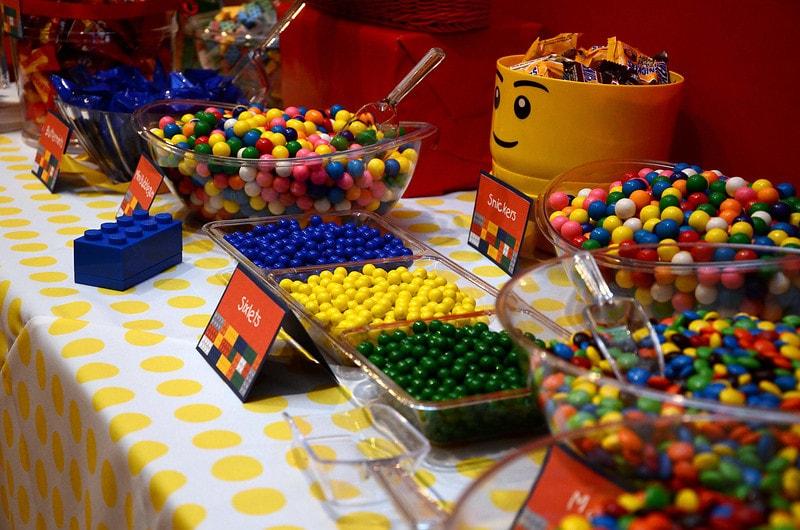 Comidas e lanches de festa coloridos, lembrando as cores das pelas da Lego.