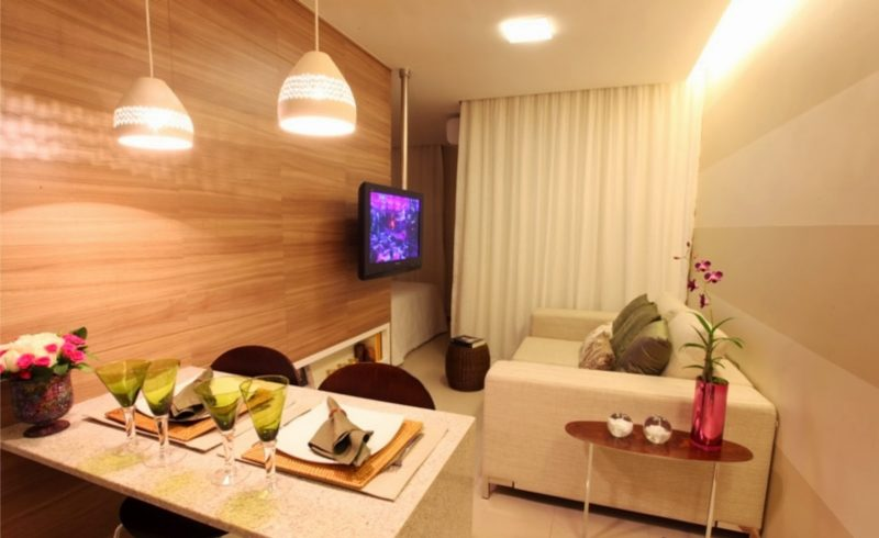 Decoração de sala integrada usando tons claros de madeira e branco