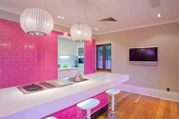 Cozinha decorada em rosa com bancada branca  luminárias pendentes