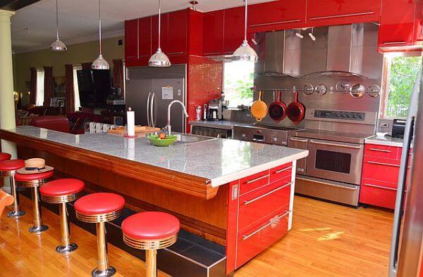 Cozinha simples com bancada, banquetas e luminárias pendentes