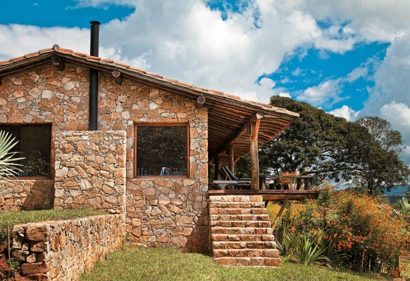 Casa no campo com fachada em pedra ferro e varanda de madeira rústica